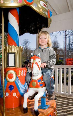 child on merry-go-round horse carousel. happy child on ride in fairground park photo
