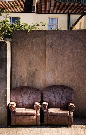 trashed: armchairs on street or pavement in urban town area.trashed furniture, rubbish or litter by the road