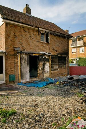 fire damage: house ruin after fire. burned down property in urban area Stock Photo