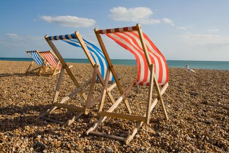 deck chair on beach in brighton. Sun lounger at the seaside in england on windy day photo