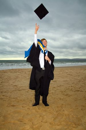 student in cap and gown or ropes. graduate from university celebrating degree  by throwing hat. male on the beach by sea photo