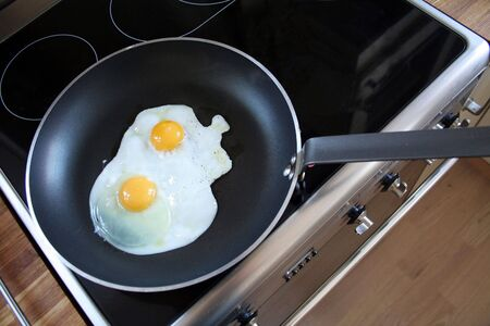 egg in frying pan. breakfast of two eggs with yellow yolks cooking on steel cooker photo