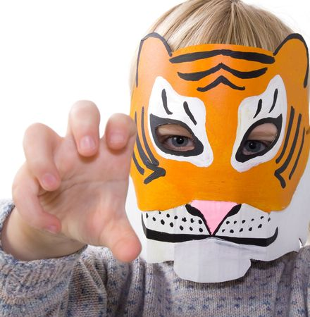 carnival festival: child with tiger mask. kid pretending to be wild animal. toddler dressed up playing and isolated on white Stock Photo