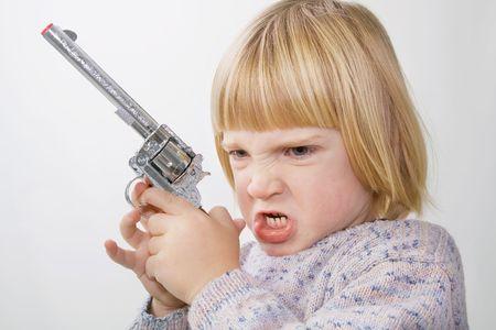 point and shoot: ni�o con pistola. ni�o con el objetivo de arma de juguete de estilo occidental Foto de archivo