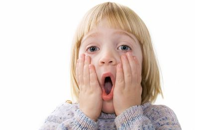 surprised child isolated on white. blond boy with expression of shock or surprise with hands to his head and open mouth