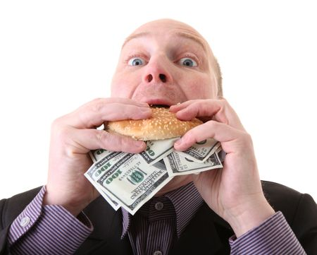 greed, businessman eating money. man eat dollars in display of avarice isolated on white.