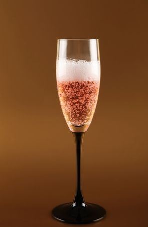 pink champagne in glass flute. bubbly alcohol fizz for celebration on gold background Stock Photo