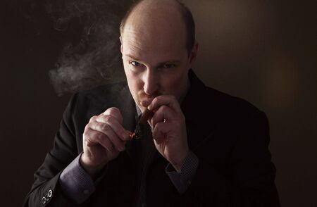 bad habit: man lighting cigar and smoking. bold white male with unhealthy bad habit or addiction Stock Photo