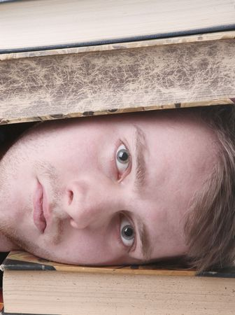 inundated: student overwhelmed and inundated with study work. male with books on head Stock Photo