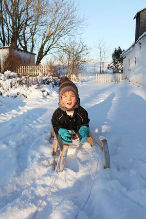 child on sledge or sleigh in winter snow. kid playing on leisure equipment having fun photo