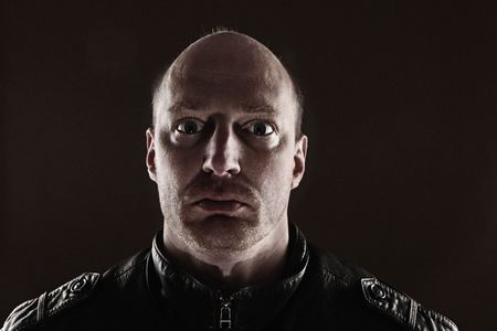 portrait of male skinhead in leather jacket lit from behind. Dark picture of bald man with stubble Stock Photo - 8267665