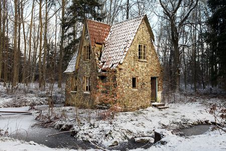 ruins is ancient: ruin in forest. lodge or small house abandoned and falling down. architecture built in flint and stone with water around or in lake in winter