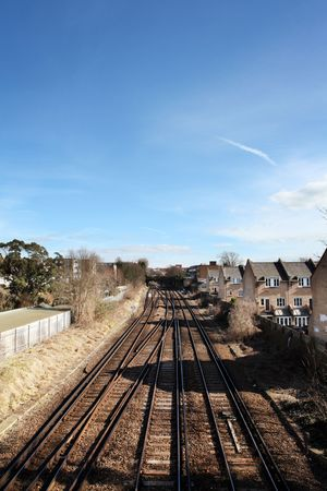 railtrack: railroad or train track running through urban city housing estate. railway next to homes and houses in England between Brighton and Hove