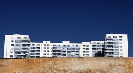 holiday apartments or hotel on top of cliffs in brighton, england. flats with balcony against blue sky