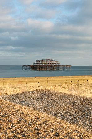 brighton burned down west pier. sussex pebble beach with groyne in foreground photo