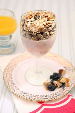 roughage: Healthy breakfast meal of yoghurt and muesli. Snack diet  meal of raisins, nuts and oats with dairy product in glass