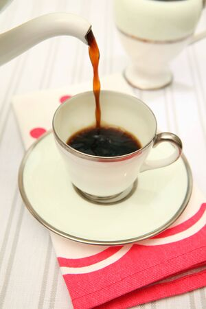 pouring black coffee into vintage or retro cup. spout with hot beverage running into China cup
