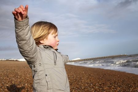 elated: child on beach with arms out enjoying feeling of freedom. kid at seaside with celebrating attitude