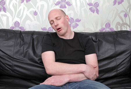 man tired and sleeping on sofa. male relaxing or napping on leather couch photo