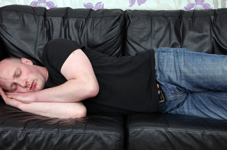 man tired and sleeping on sofa. male relaxing or napping on leather couch