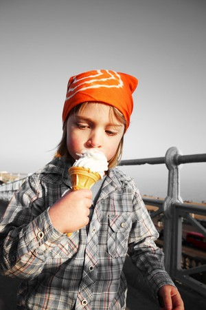 child eating icecream cone. boy with orange bandana eats frozen dairy snack  photo