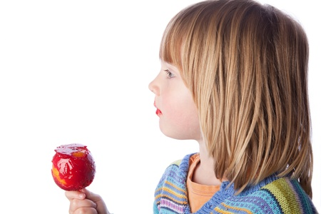 taffy apple: child eating toffee apple or taffy apple isolated on white. kid with sweet seasonal candy fruit snack