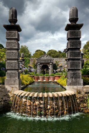 garden park with wooden architecture and water and fountain. ornamental flower garden photo