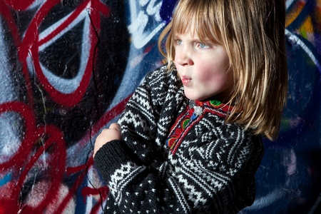 child in front of graffiti wall in urban area. Cool young boy by street art in deprived town area photo