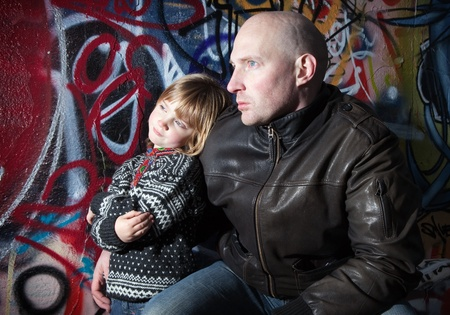 fatherhood: father and son in front of graffiti wall. Urban portrait of fatherhood or family. street art and two males