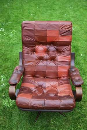 recliner: retro leather designer armchair. danish 70s recliner furniture on grass lawn