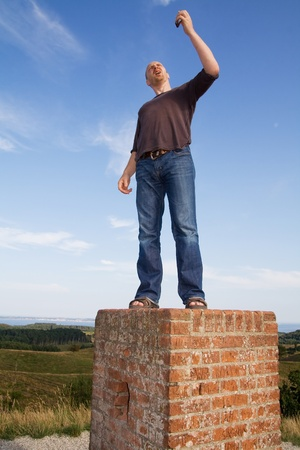 man standing on pedestal finding connection for mobile phone photo