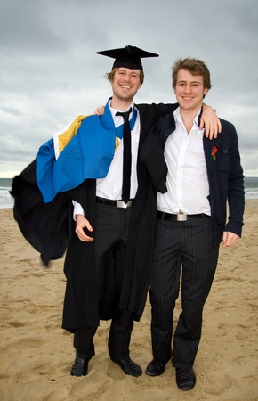 Student graduating with cap and gown on beach. University graduate celebrating photo