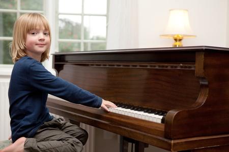 tocando piano: tocando música de piano, niño practicando el instrumento clásico. Niño rubio en el desempeño de salón Foto de archivo