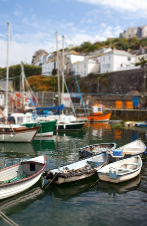 Fishing boats in harbor in cornish village of Mousehole Cornwall English holiday destination with water and maritime vessels in port photo