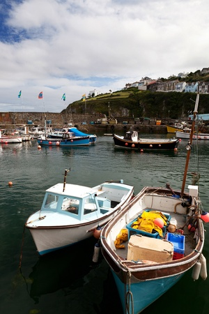 cornish: Fishing boats in harbor in cornish village of Mousehole Cornwall English holiday destination with water and maritime vessels in port Stock Photo