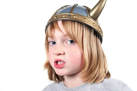 confrontational: Angry child with viking helmet. boy isolated on white with expression of aggression. blond kid dressed up Stock Photo