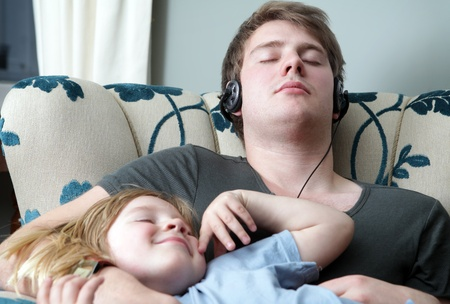 sleeping in chair at home. brothers resting, one teenager with headphones and child with long blond hair. family relaxing photo