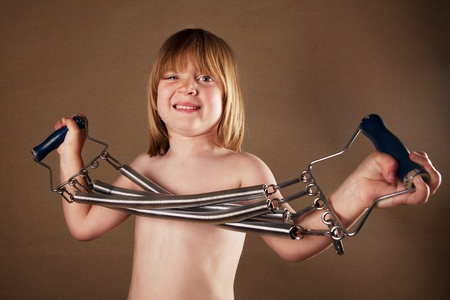 coil: Child exercise with gym equipment. studio image of boy with spring coil fitness device on brown studio background