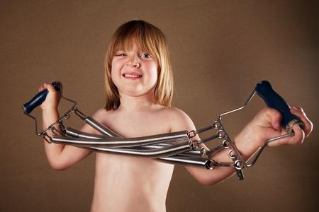 spirale: Kinder-Training mit Fitnessgeräten. Studio Bild Junge mit Spiralfeder Fitness-Gerät auf braunem Hintergrund Studio