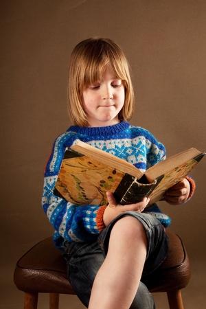 Bambino leggere il libro. Image Studio di ragazzo biondo su sfondo marrone, studiando un libro di testo