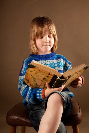 Child reading book. studio image of blond boy against brown background studying a text book