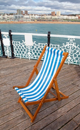 brighton beach: deck chair on Brighton pier boardwalk. empty sun lounger and views over sea towards cityscape of holiday resort in England