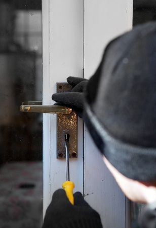 Breaking and entering home or house, Burglar with screwdriver force open door. Thief attempting to breach security Stock Photo - 12186924