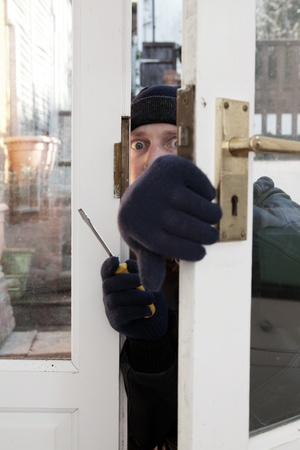 Breaking and entering home or house, Burglar with screwdriver force open door. Thief attempting to breach security Stock Photo - 12186929