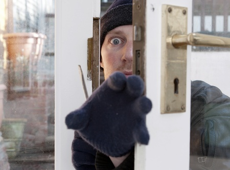 Breaking and entering home or house, Burglar with screwdriver force open door. Thief attempting to breach security photo