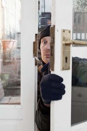 Breaking and entering home or house, Burglar with screwdriver force open door. Thief attempting to breach security Stock Photo - 12325466