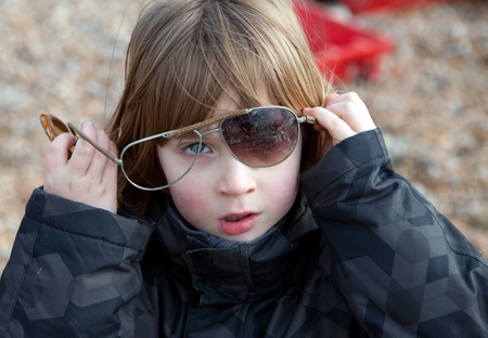 come up to: Child playing with broken sunglasses. blond boy outdoors with glasses