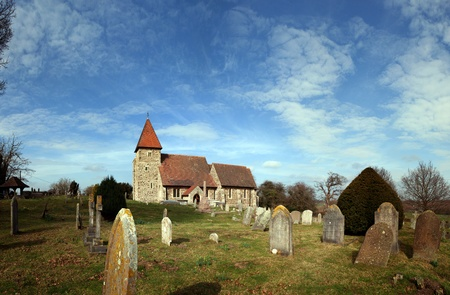 Church in graveyard. English village church Saint Lawrence in Guestling. Traditional medieval place of Christian worship in England photo