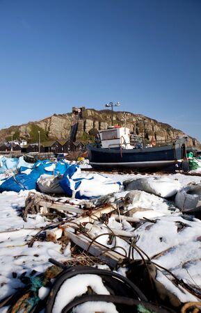 hastings: fishing industry, trawler or fishing boat on the beach in seaside resort of Hastings in England. South UK shoreline in winter snow Editorial