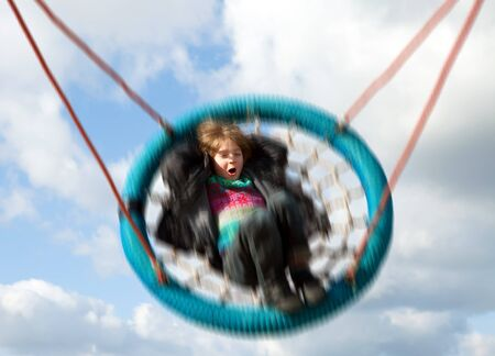amusement park ride: Child on swing against blue sky. Swinging boy moving at speed on playground ride